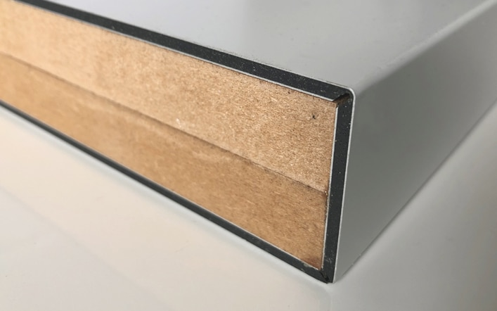 A sheet of Dibond with a V groove and bent around MDF