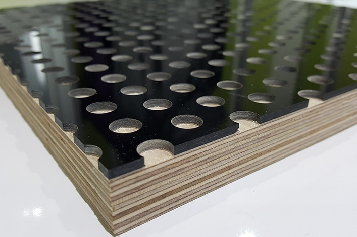 A close up showing perforated black acrylic bonded to a birch plywood panel