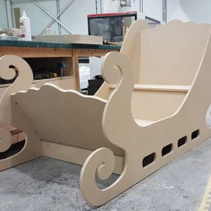 A Christmas wedding photo booth made from MDF in the shape of santas sleigh the sleigh is yet to be painted