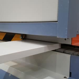 Close up of a piece of white melamine board going though an edge banding machine