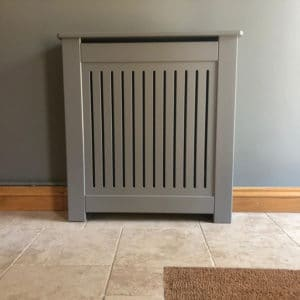 A bespoke grey painted MDF radiator cover in situ on a tiled floor