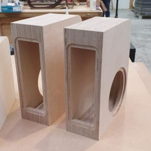 Two Bespoke speaker cabinets made from CNC cut layers of birch plywood sitting on a workshop bench