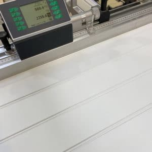 A close up photo showing a pre-primed bead and butt MDF panel being cut on a panel saw. The saw digital fence is in view