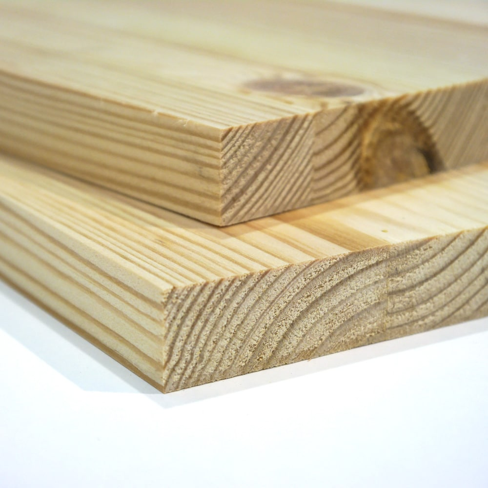 Two pieces of edge glued Pine board on a white background
