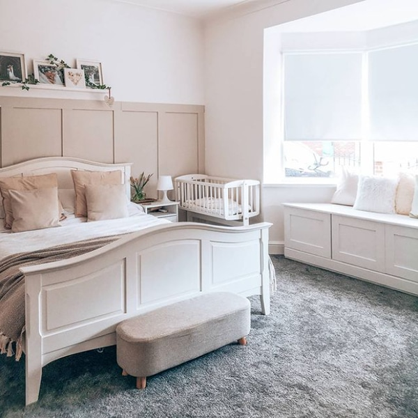 a bed sat in front of beige wall panelling in a neutral themed bedroom