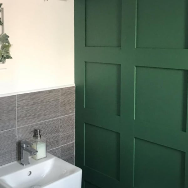green cloakroom shaker style wood panelling with a small sink and grey tiles