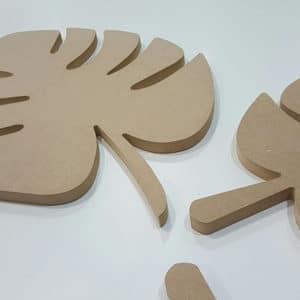 Palm leaf MDF shapes laying on a white panel