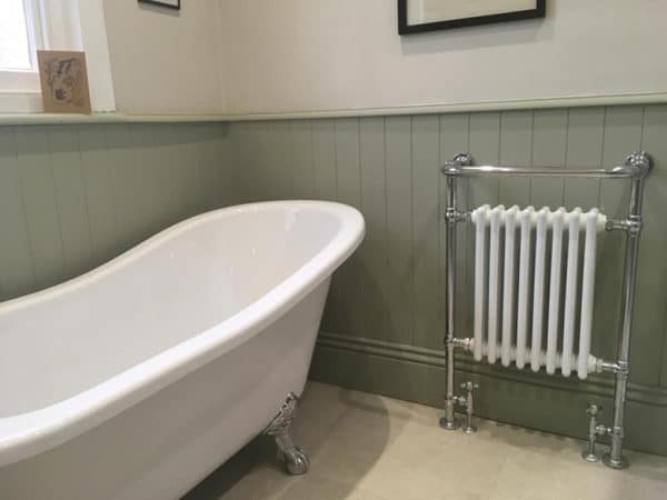 painted olive green bathroom wall panelling with a free-standing roll top bath and a column radiator