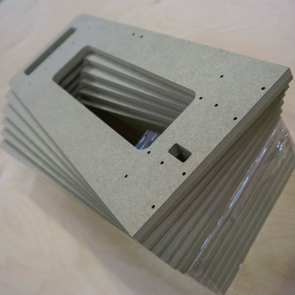 A stack of MR MDF panels cut to shape and drilled on a CNC router
